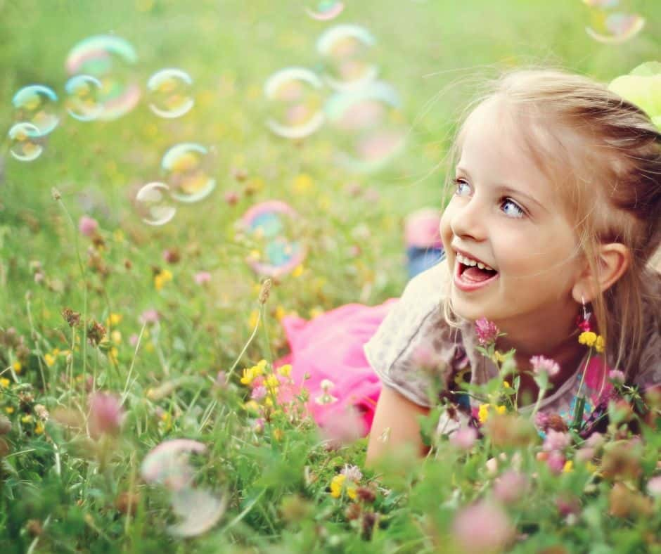 little girl in grass watching bubbles