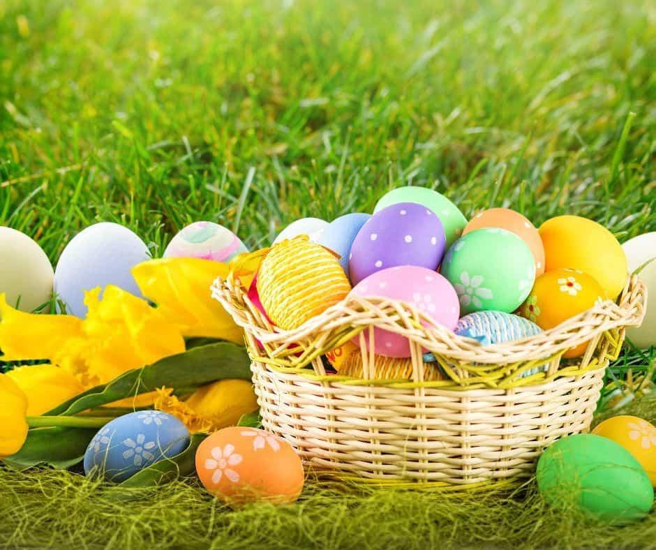 Easter eggs in wicker basket set in grass