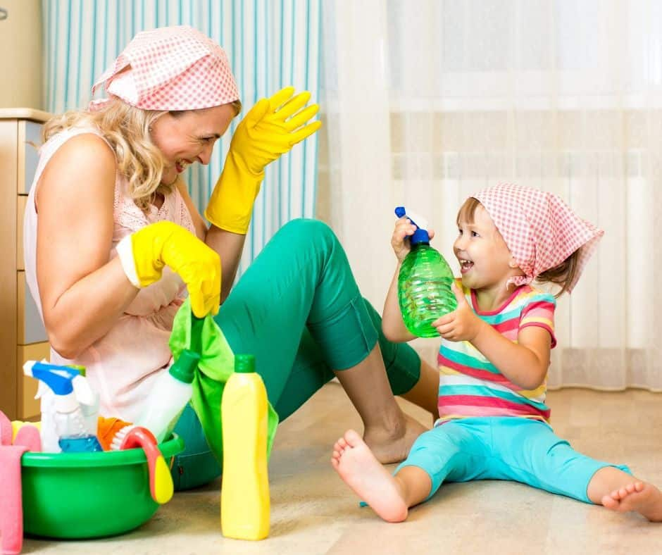 mom and toddler laughing while dressed to clean the house and spraying each other with spray bottles