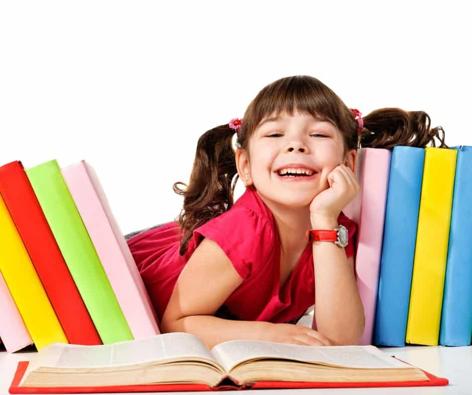 girl smiling surrounded by books