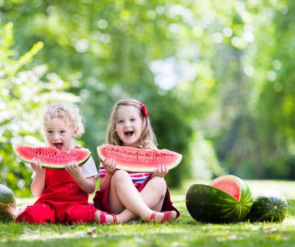 two girls enjoying watermelon on a summer picnic