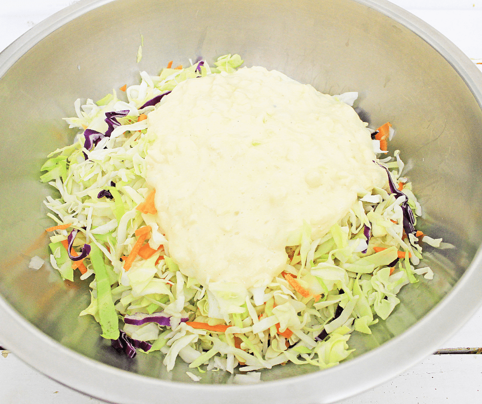 Mixing bowl with fresh coleslaw mix topped with pineapple coleslaw dressing