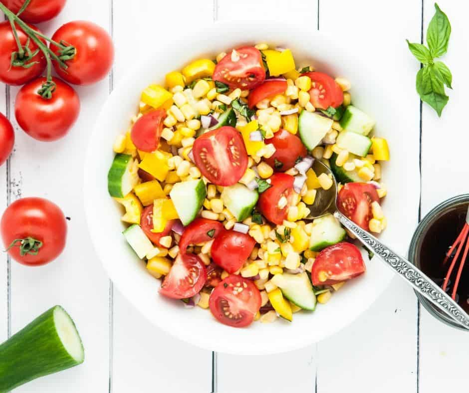 bowl of summer corn salad surrounded by fresh vegetables