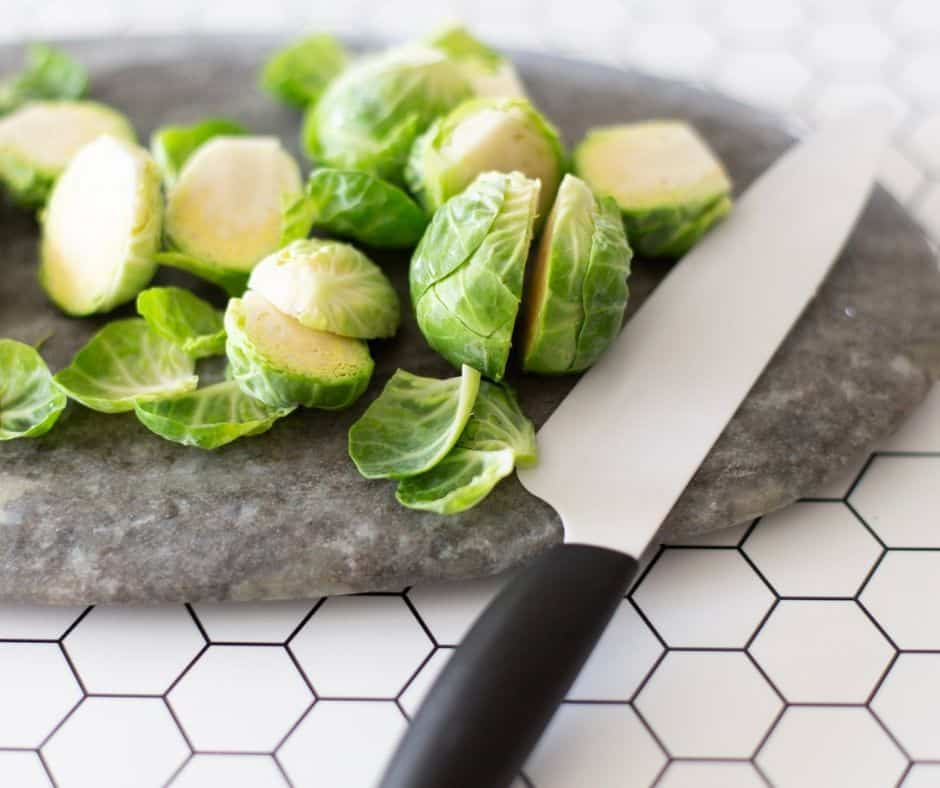 knife and cutting board with halved brussel sprouts being prepped for roasting