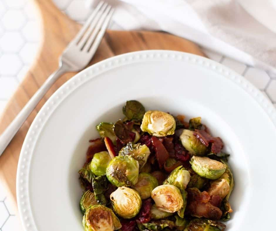 bacon roasted brussel sprouts in a white bowl on a wooden cutting board
