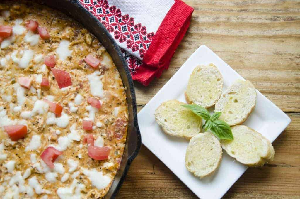 low carb chicken parmesan skillet dip with a plate of bread and pretty towel