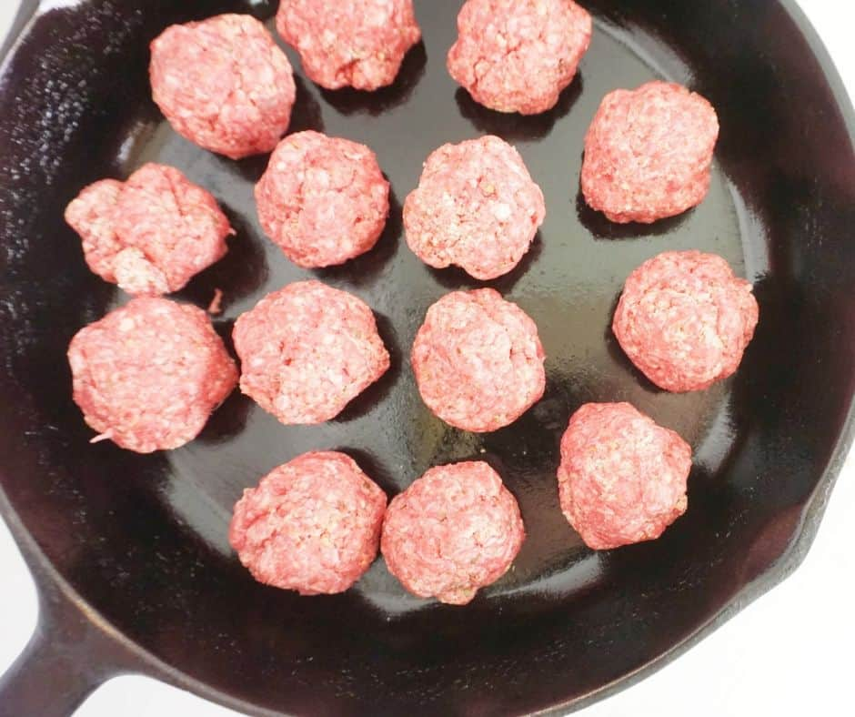 uncooked meatballs in a cast iron skillet