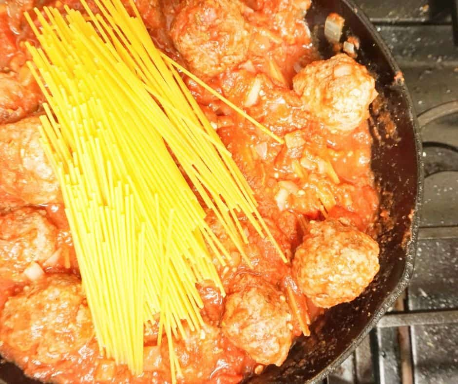 cooking spaghetti in a skillet with meatballs for an easy one dish weeknight family meal idea