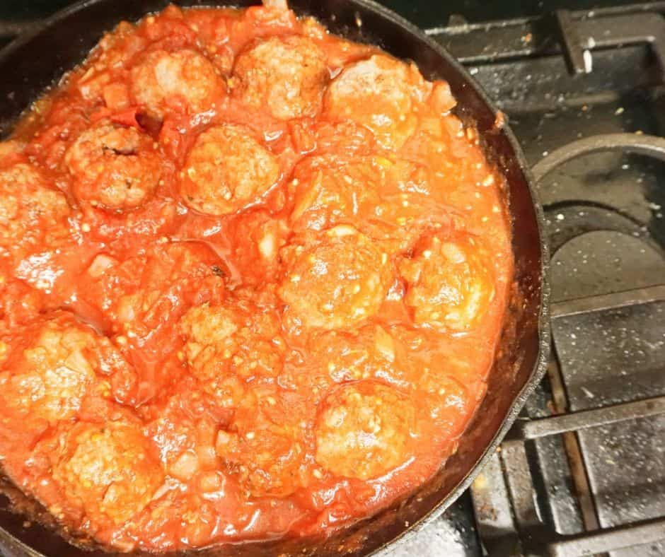 meatballs cooking in sauce in skillet on stovetop