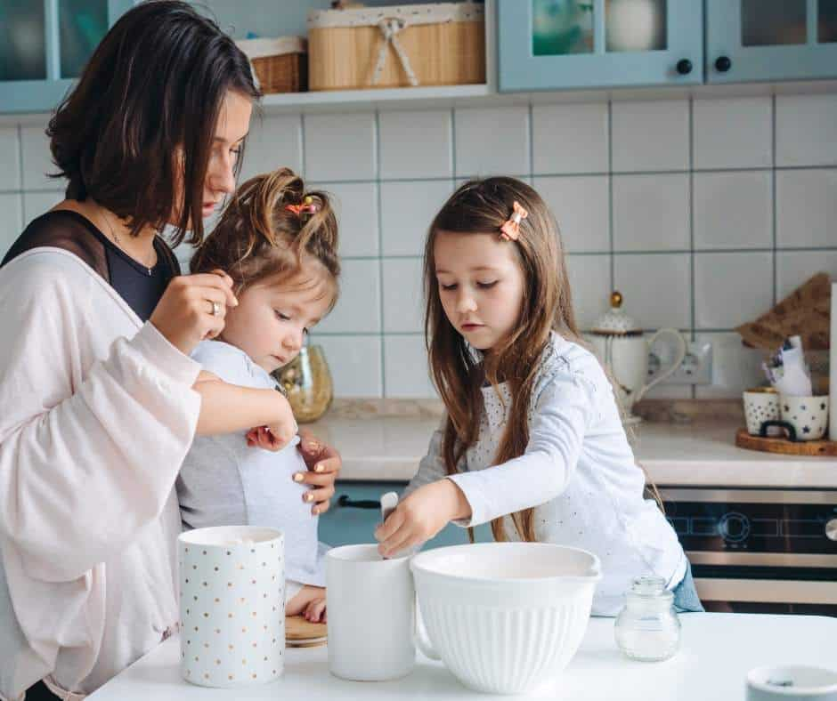 mom cooking with her two preschool aged daughters