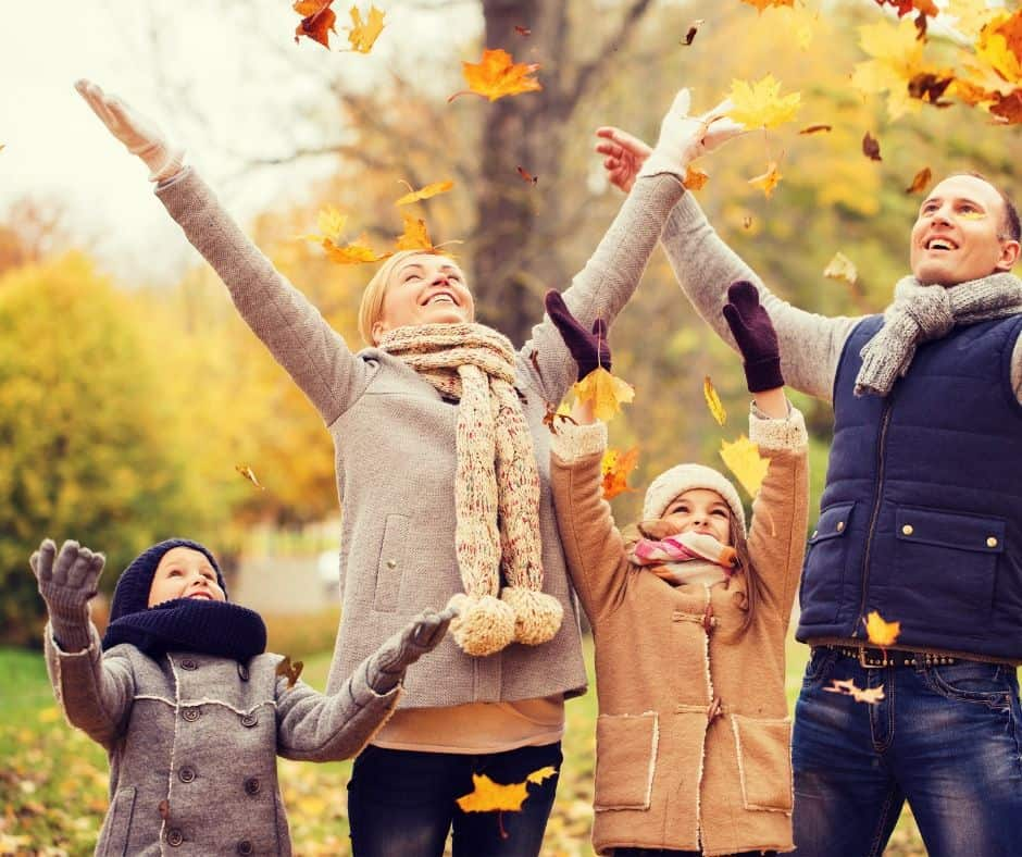 family playing in fall leaves together