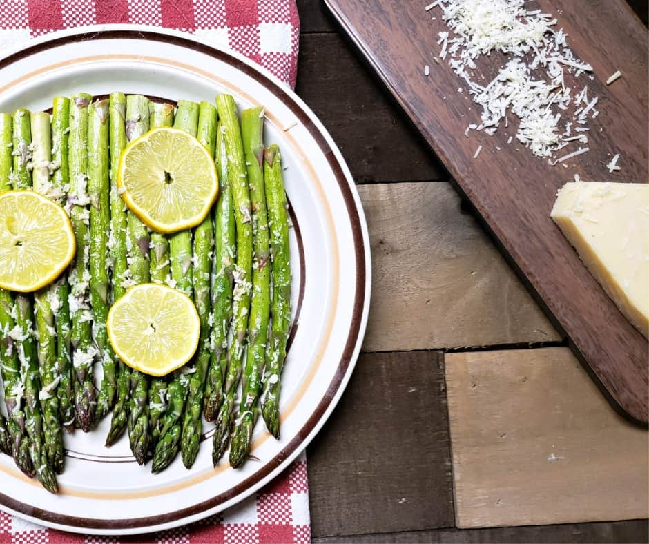 plated keto side dish of garlic roasted asparagus topped with lemon and parmesan cheese