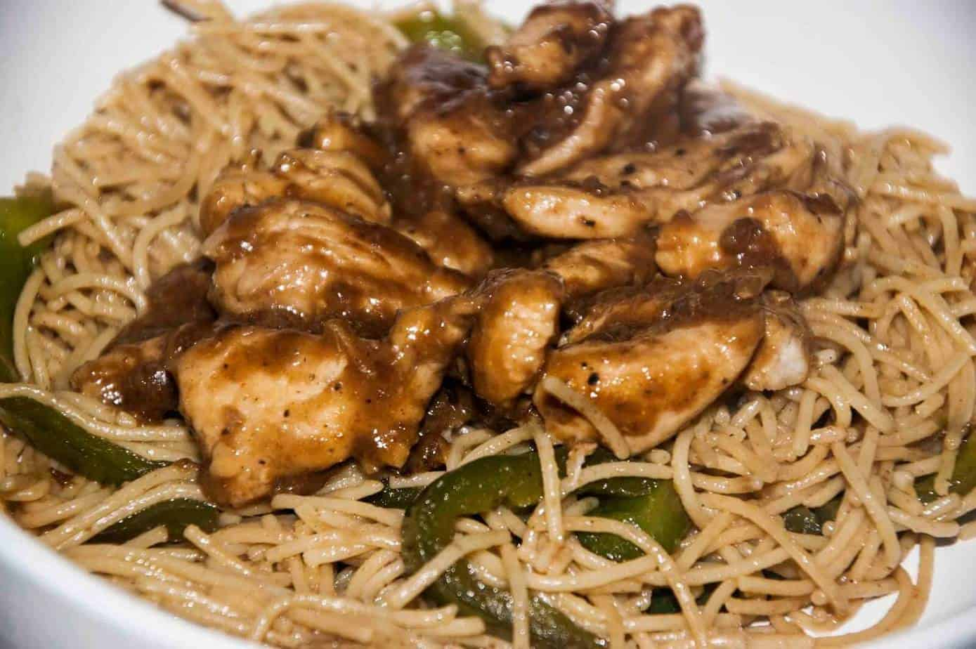 Mongolian Chinese chicken tossed with peppers and noodles on a white plate