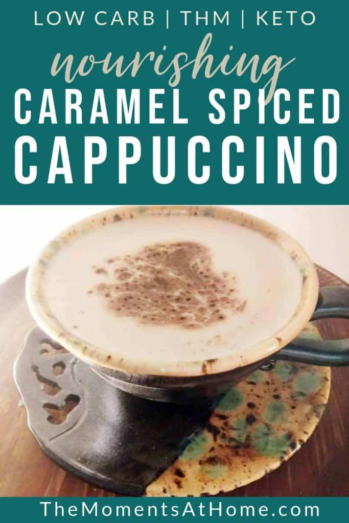 """text: """" low carb keto caramel spiced cappuccino by The Moments At Home"""" with photo of a cappuccino in a pottery mug"""