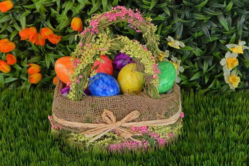 Easter Basket on grass in garden filled with colored eggs and no candy