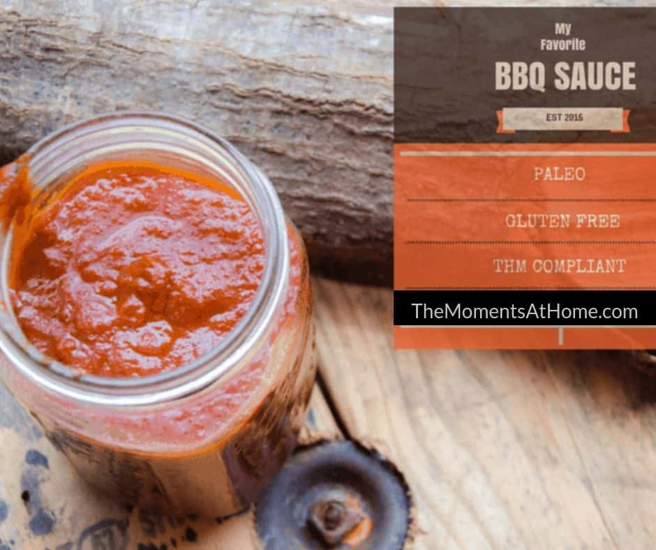 healthy homemade BBQ sauce that is sugar free in a jar near a log on a wooden table