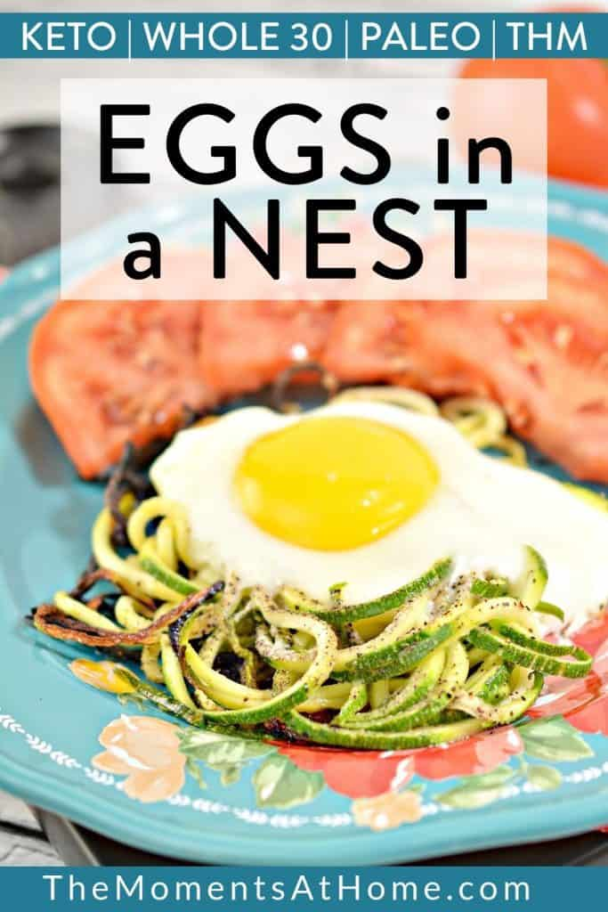 """sunny side up egg on zoodles on a blue plate with tomato wedges with text """"keto, paleo, whole 30, THM zucchini eggs in a nest"""" by the moments at home"""