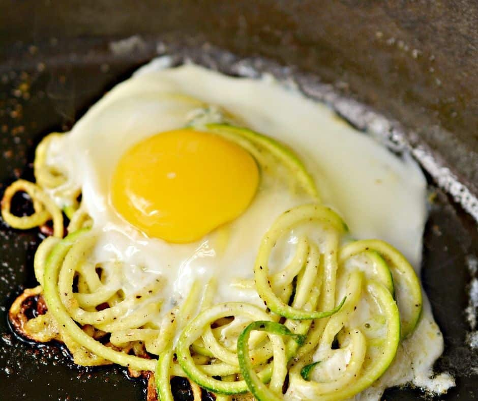 sunny side up egg cooking on top of a bed of zoodles in a cast iron skillet