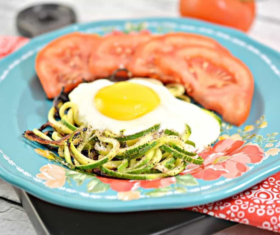 Keto Eggs in a next on top of zoodles with tomato wedges on a plate