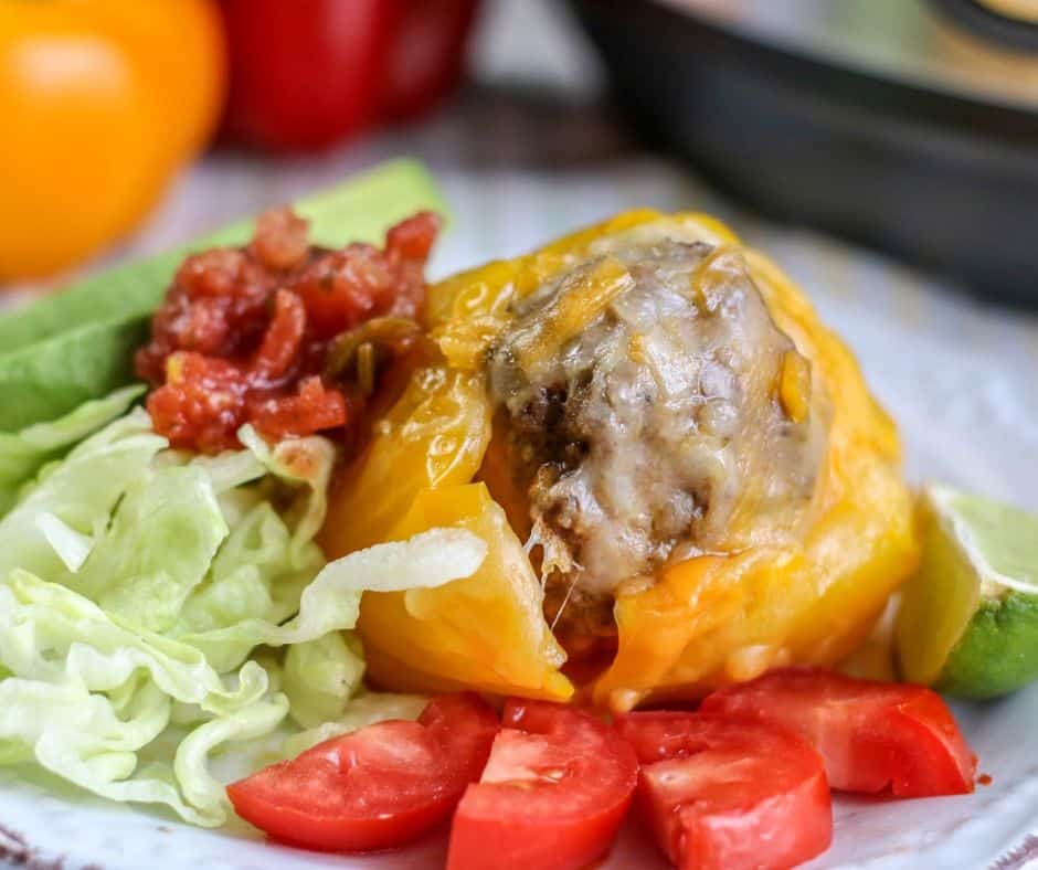 yellow bell pepper stuffed with Mexican flavored beef on a plate with the Instant Pot in the background and a salad