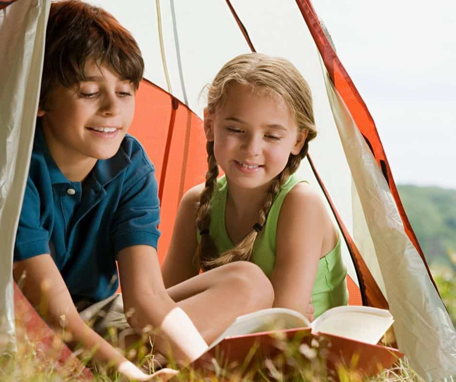 two kids reading historical fiction books outside in a tent