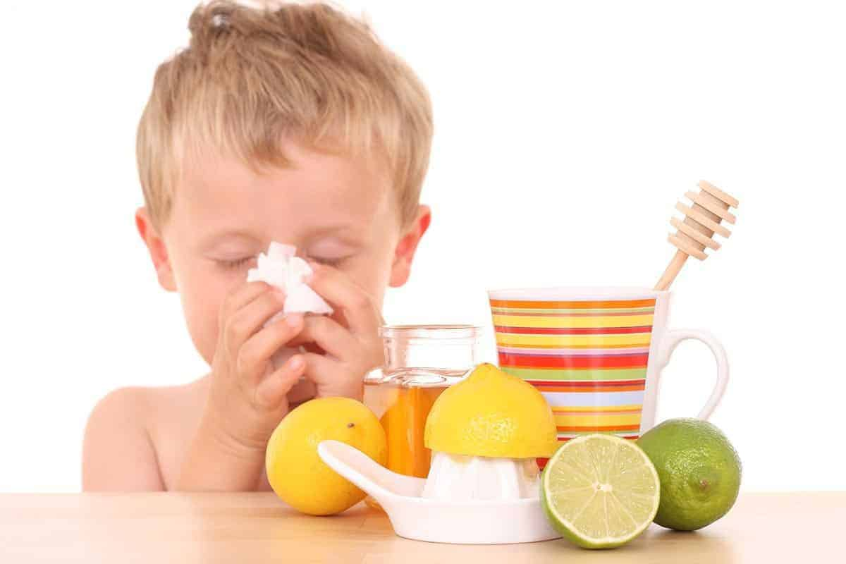 child wiping nose and has lemon and honey