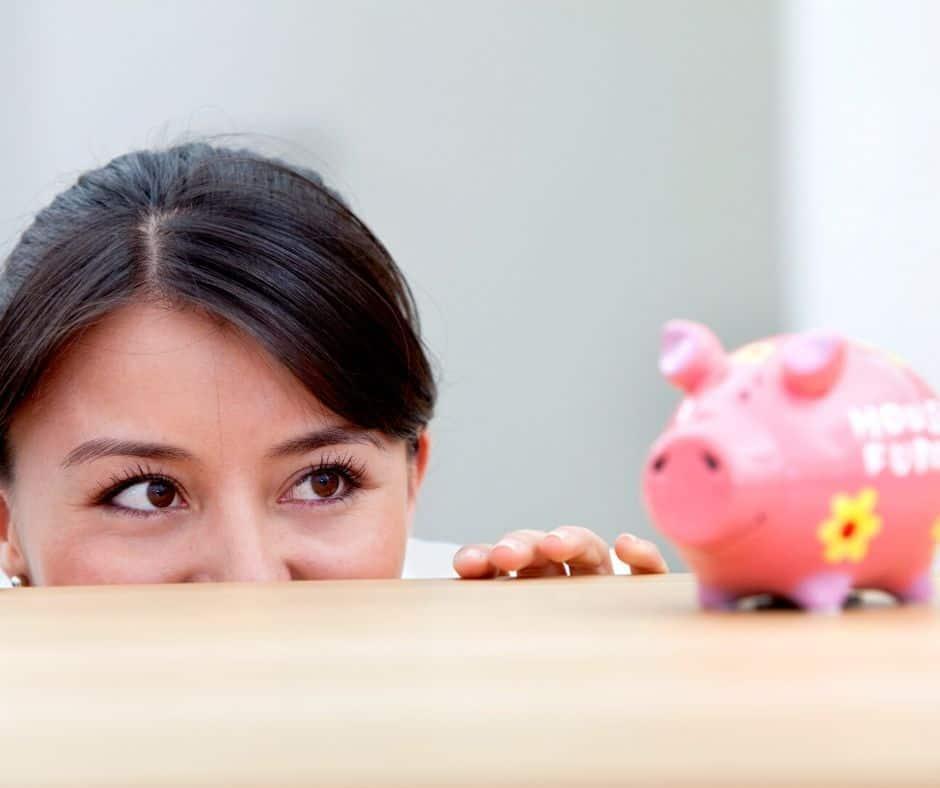 woman smiling at piggy bank