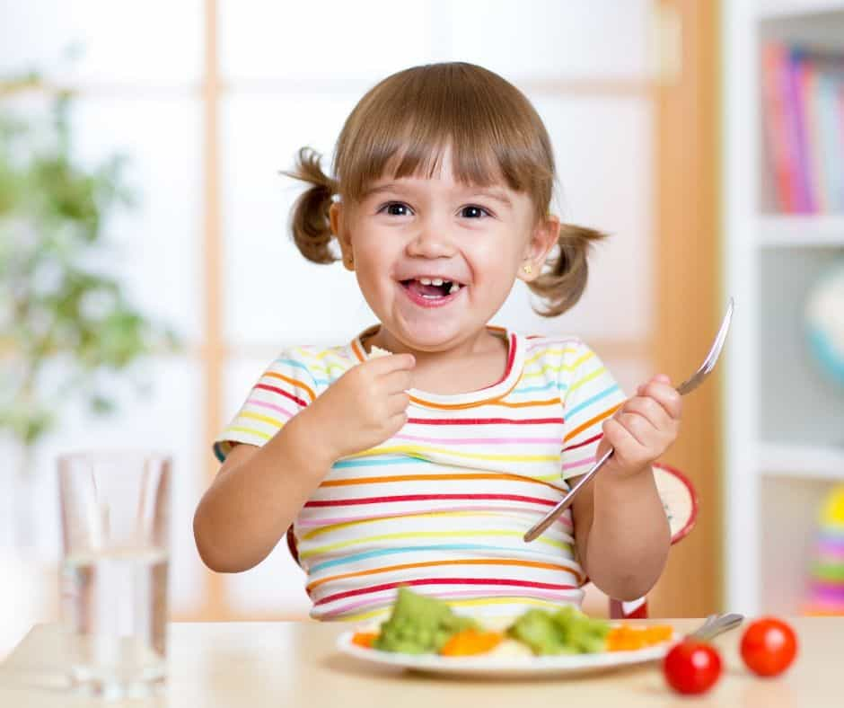 toddler eating vegetables with smile