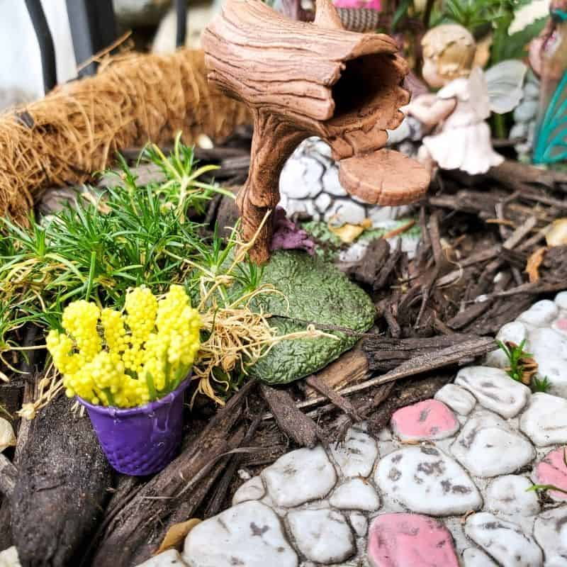 close up of homemade fairy planters outside of DIY fairy house in a fairy garden
